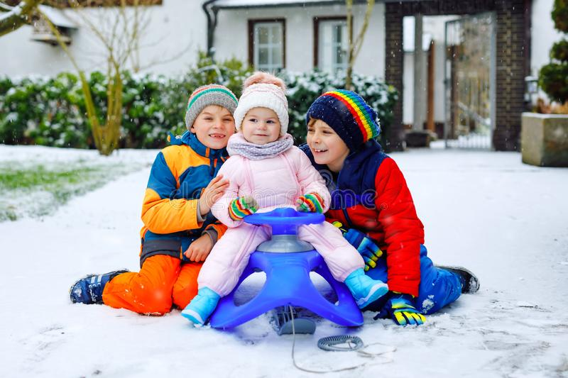 Two little kid boys and cute toddler girl sitting together on sledge. Siblings, brothers and baby sister enjoying sleigh. Two little kid boys and cute toddler stock photography