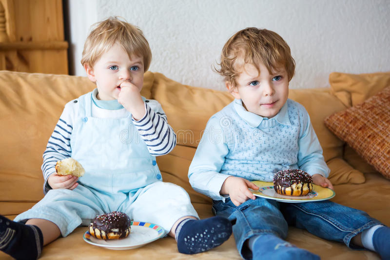 Two little kid boys eating sweet cakes together. Family of two brothers royalty free stock photo