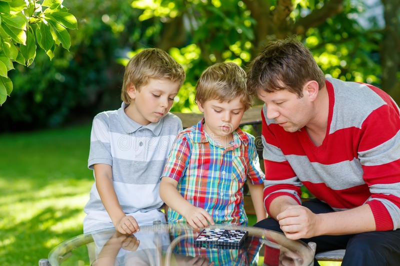 Two little kid boys and father playing together checkers game royalty free stock photography
