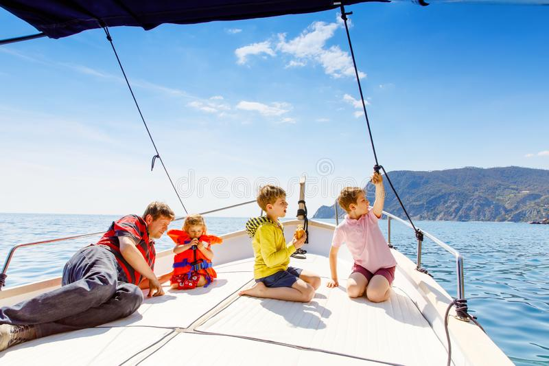 Two little kid boys, father and toddler girl enjoying sailing boat trip. Family vacations on ocean or sea on sunny day royalty free stock photo