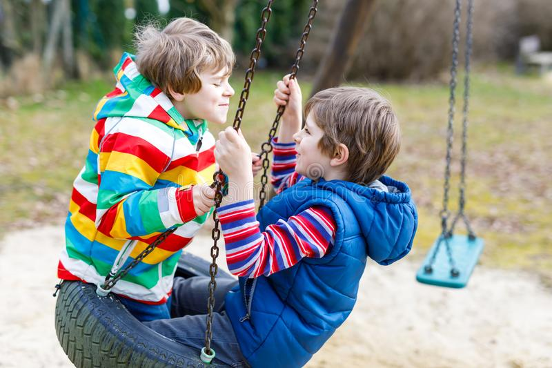Two little kid boys having fun with chain swing on outdoor playground. Children, best friends and siblings swinging on warm sunny spring or autumn day. Active stock images