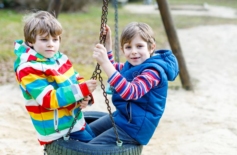 Two little kid boys having fun with chain swing on outdoor playground. Children, best friends and siblings swinging on warm sunny spring or autumn day. Active stock photo