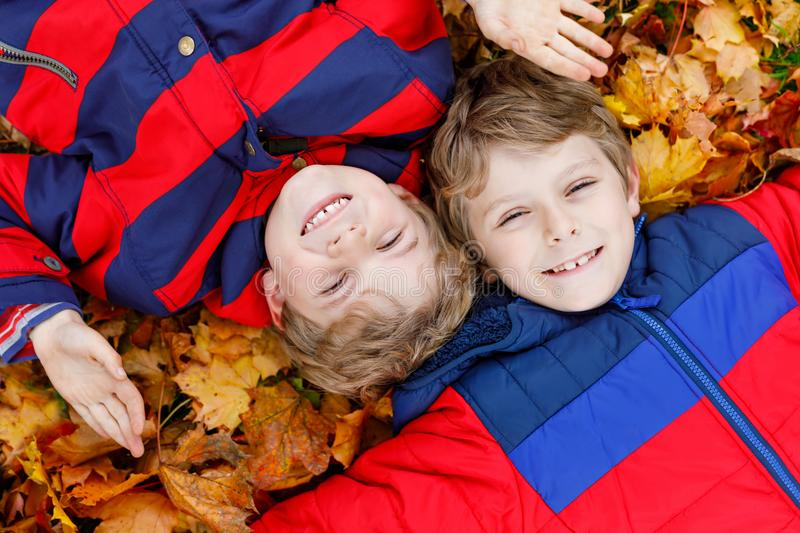 Two little kid boys lying in autumn leaves in colorful fashion fall clothing. royalty free stock photo