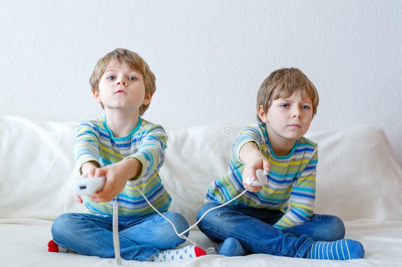 Two little kid boys playing video game at home royalty free stock photography