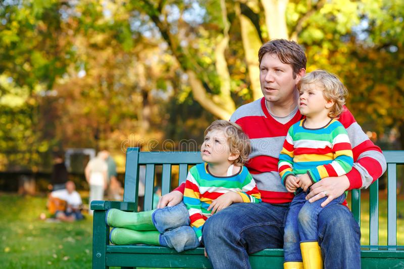 Two little kid boys and young father sitting together in colorful clothing on bench. Cute healthy children, siblings and stock photos