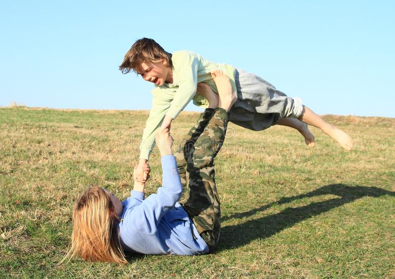 Two kids playing and exercising yoga on meadow. Two little kids - barefoot girl and boy exercising partner yoga - Super Yogi - pose to transition into from royalty free stock image