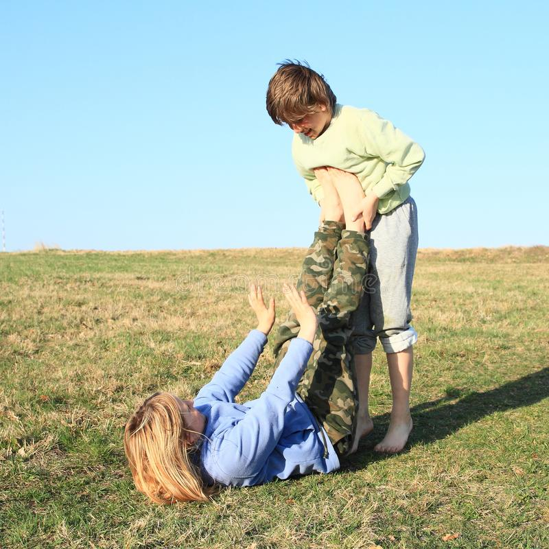 Two kids playing and exercising yoga on meadow. Two little kids - barefoot girl and boy exercising partner yoga - Super Yogi - pose to transition into from stock image