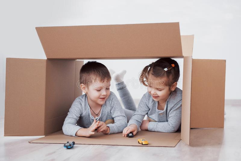 Two a little kids boy and girl playing small cars in cardboard boxes. Concept photo. Children have fun. Concept photo. Two a little kids boy and girl playing stock photography