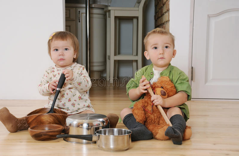 two little kids boy and girl sitting on the kitchen floor playing with pots royalty free stock photography