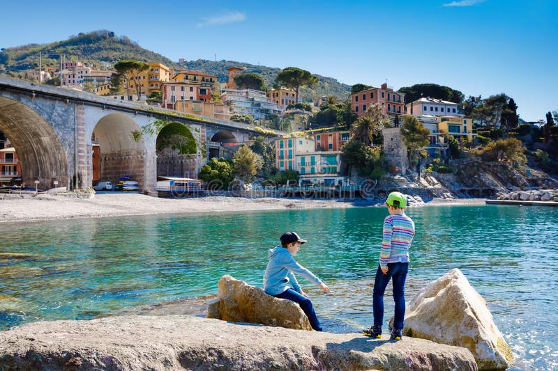 Two little kids boys climbing on stones on beach of Mediterranean sea in Liguria region, Italy. Siblings brothers in royalty free stock photos