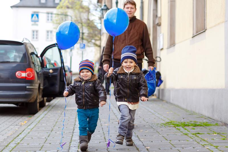 Two little kids boys and dad playing with blue air balloons outdoors. Happy twins and toddler brothers and father, young. Two little kids boys playing with blue stock photos