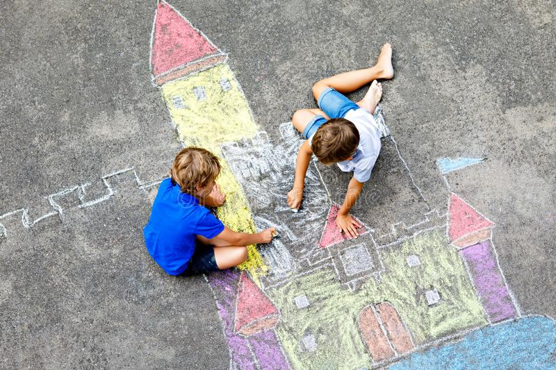 Two little kids boys drawing knight castle with colorful chalks on asphalt. Happy siblings and friends having fun with royalty free stock photography