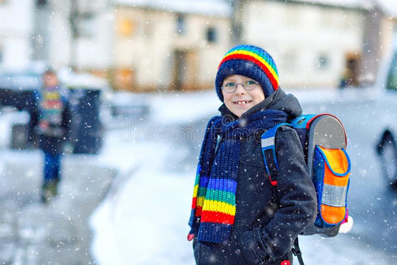 Two little kids boys of elementary class walking to school during snowfall. Happy children having fun and playing with. First snow. Siblings ans friends with stock images
