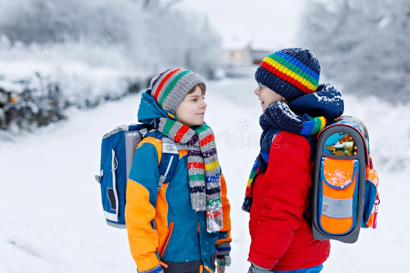 Two little kids boys of elementary class walking to school during snowfall royalty free stock photos