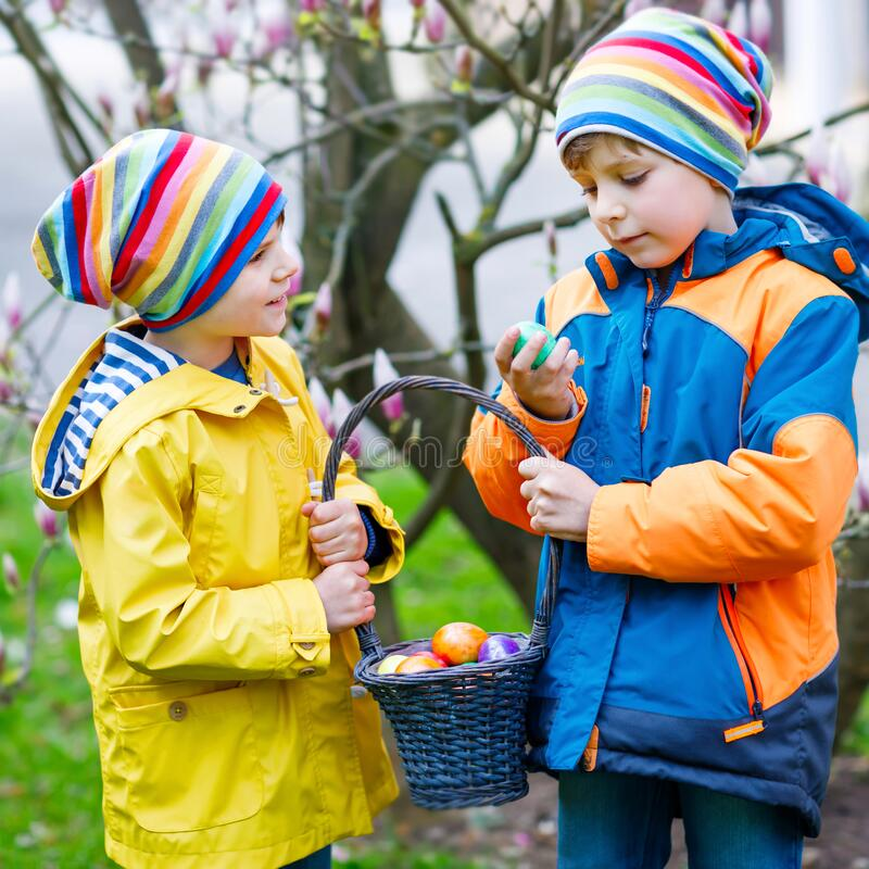 Two little kids boys and friends making traditional Easter egg hunt in spring garden, outdoors. Siblings having fun with royalty free stock photo