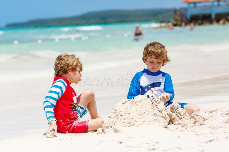 Two little kids boys having fun with building a sand castle on tropical beach of carribean island. Children playing together on their vacations Twins, Happy stock image