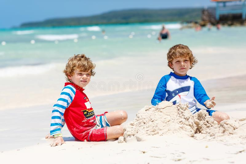 Two little kids boys having fun with building a sand castle on tropical beach of carribean island. Children playing together on their vacations Twins, Happy stock photo