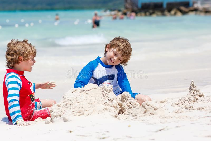 Two little kids boys having fun with building a sand castle on tropical beach of carribean island. Children playing together on their vacations Twins, Happy royalty free stock photo