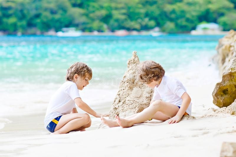 Two little kids boys having fun with building a sand castle on tropical beach of Seychelles. children playing together stock photography