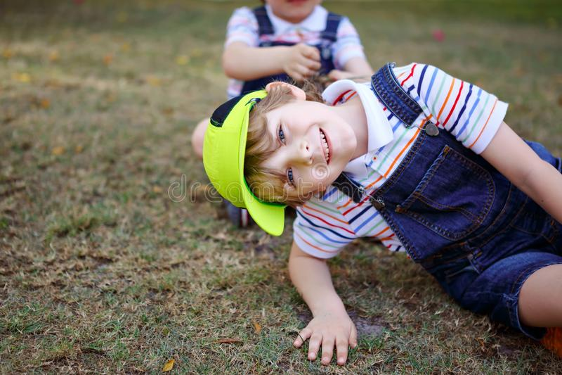 Two little kids boys having fun in a park, happy best friends playing, friendship concept. Siblings brothers, twins in stock image