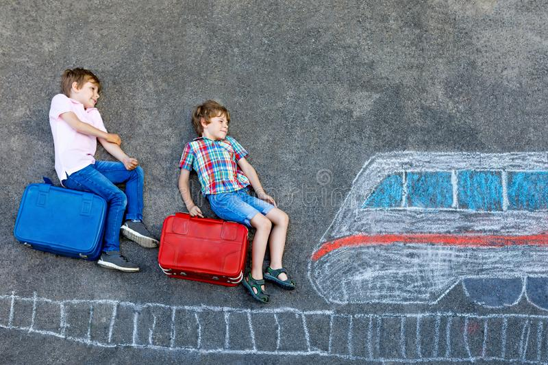 Two little kids boys having fun with train picture drawing with colorful chalks on asphalt. Children having fun with. Chalk and crayon painting. going on royalty free stock images