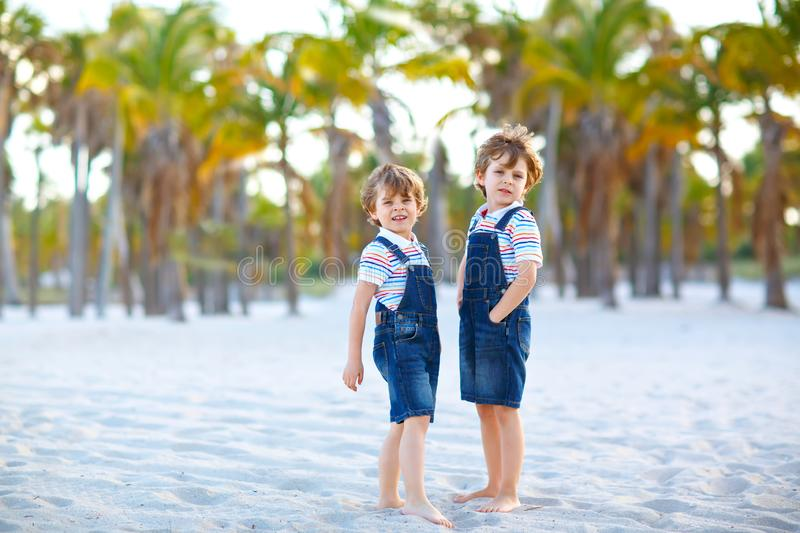 Two little kids boys having fun on tropical beach, happy best friends playing, friendship concept. Siblings brothers. Twins in family look with palms trees on stock images