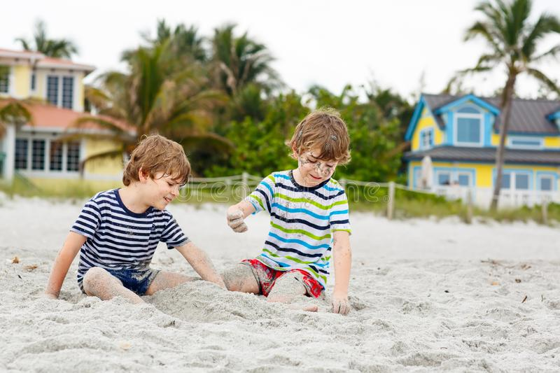 Two little kids boys having fun on tropical beach, happy best friends playing, friendship concept. Siblings brothers royalty free stock photos