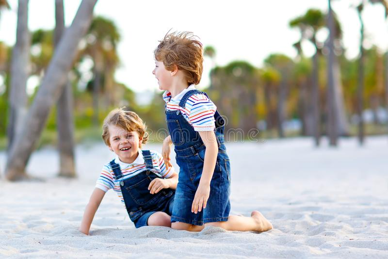 Two little kids boys having fun on tropical beach, happy best friends playing, friendship concept. Siblings brothers stock images