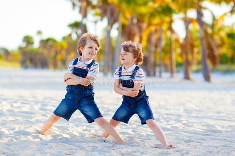 Two little kids boys having fun on tropical beach stock photos