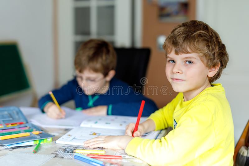 Two little kids boys at home making homework. Little concentrated children writing with colorful pencils, indoors. Elementary school and education. Siblings royalty free stock image