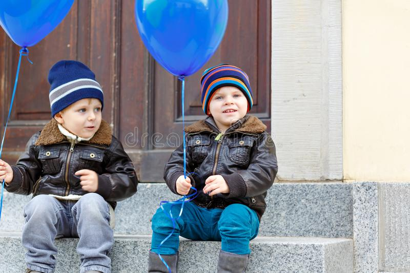 Two little kids boys playing with blue air balloons outdoors. Happy twins and toddler brothers smiling and laughing royalty free stock photos