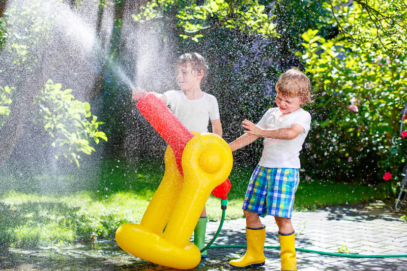 Two little kids boys playing with a garden hose water sprinkler. Two little kids boys playing with a garden hose sprinkler on hot and sunny summer day. Children stock photography