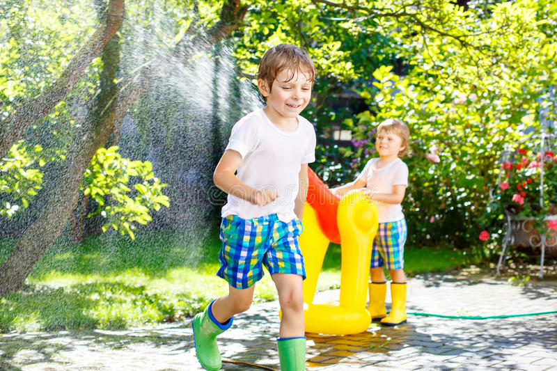 Two little kids boys playing with a garden hose water sprinkler. Two little kids boys playing with a garden hose sprinkler on hot and sunny summer day. Children stock photos