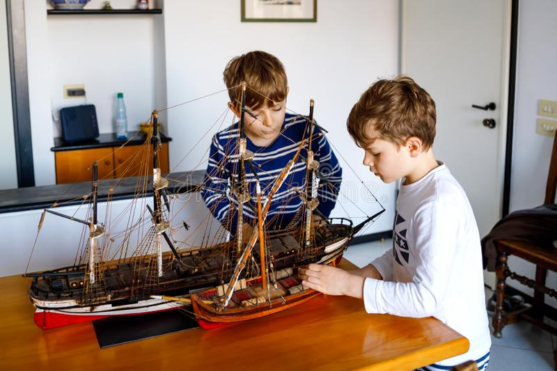 Two little kids boys playing with sailing ship model indoors. Excited children, siblings and best friends with yacht stock images
