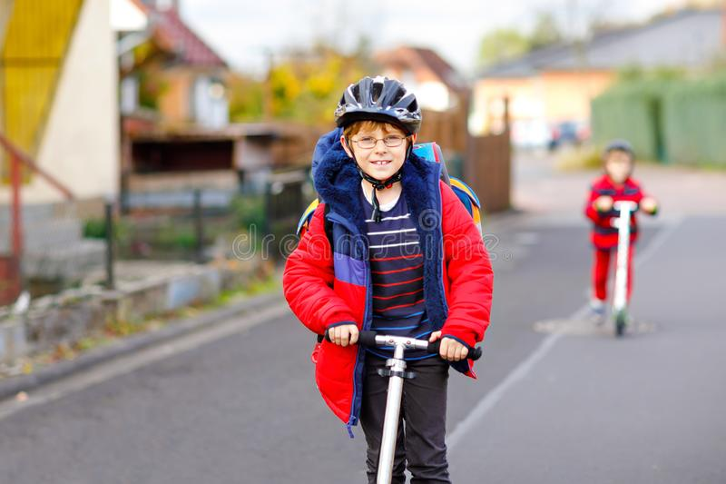 Two little kids boys riding on push scooters on the way to or from school. Schoolboys of 7 years driving through rain. Puddle. Funny siblings and best friends royalty free stock photography