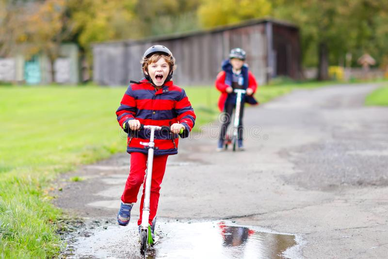 Two little kids boys riding on push scooters on the way to or from school. Schoolboys of 7 years driving through rain. Puddle. Funny siblings and best friends royalty free stock photo