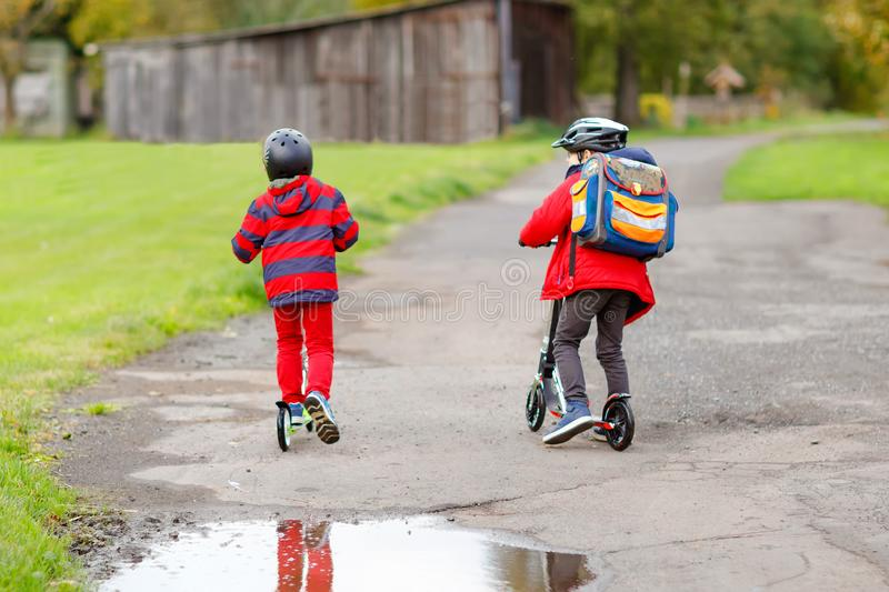 Two little kids boys riding on push scooters on the way to or from school. Schoolboys of 7 years driving through rain. Puddle. Funny siblings and best friends stock photo