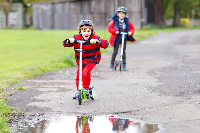 Two little kids boys riding on push scooters on the way to or from school. Schoolboys of 7 years driving through rain. Puddle. Funny siblings and best friends stock image