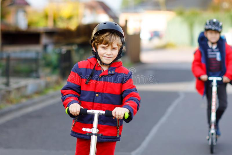 Two little kids boys riding on push scooters on the way to or from school. Schoolboys of 7 years driving through rain. Puddle. Funny siblings and best friends royalty free stock images