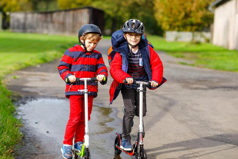 Two little kids boys riding on push scooters on the way to or from school. Schoolboys of 7 years driving through rain. Puddle. Funny siblings and best friends stock photography