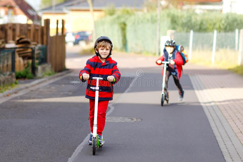 Two little kids boys riding on push scooters on the way to or from school. Schoolboys of 7 years driving through rain. Puddle. Funny siblings and best friends royalty free stock photos