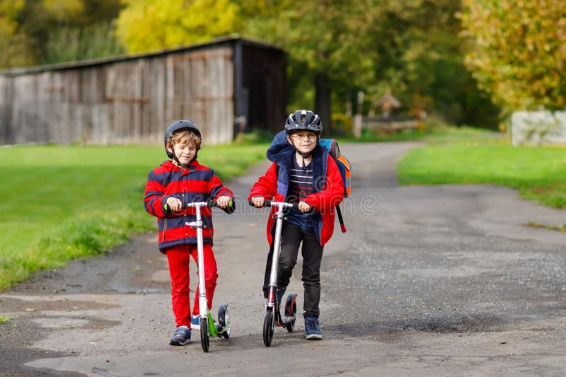 Two little kids boys riding on push scooters on the way to or from school. Schoolboys of 7 years driving through rain royalty free stock image