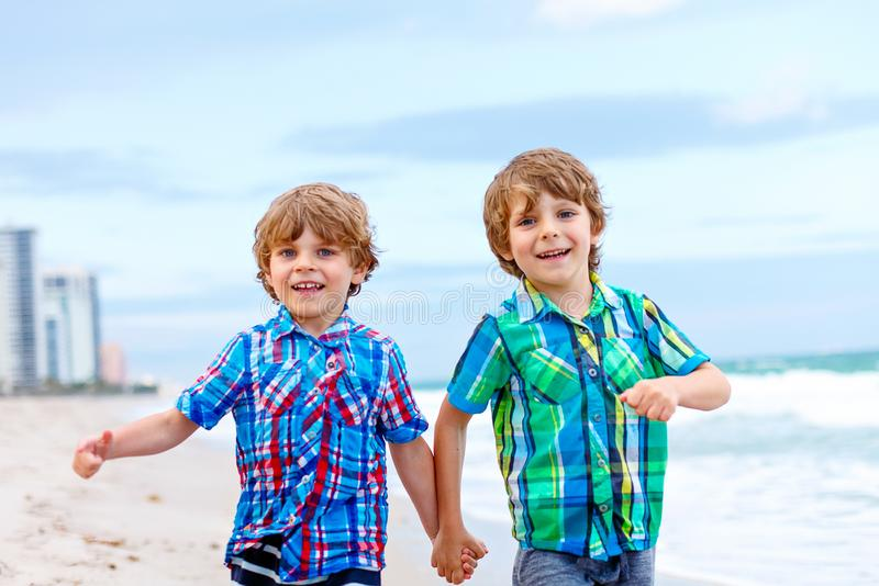 Two little kids boys running on the beach of ocean royalty free stock photo