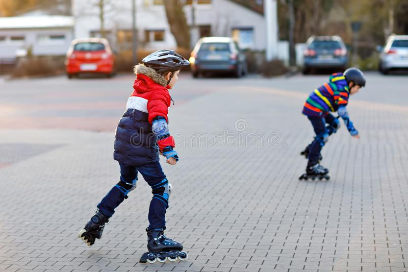 Two little kids boys skating with rollers in the city. Happy children, siblings and best friends in protection safety. Clothes. Active schoolboys making sports stock photography