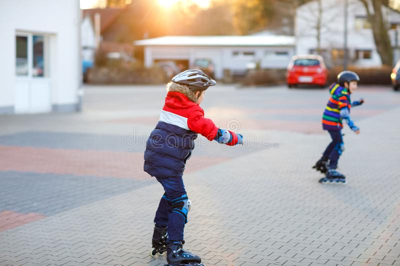 Two little kids boys skating with rollers in the city. Happy children, siblings and best friends in protection safety. Clothes. Active schoolboys making sports stock photos
