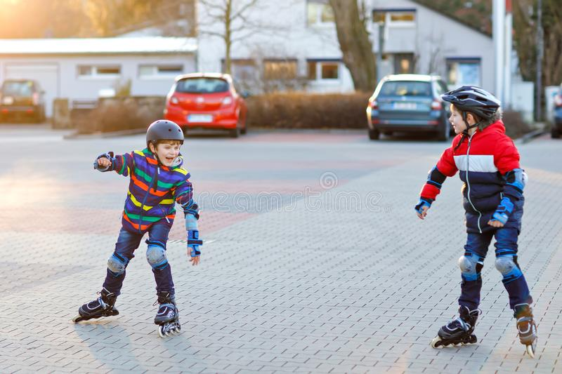Two little kids boys skating with rollers in the city. Happy children, siblings and best friends in protection safety. Clothes. Active schoolboys making sports stock images
