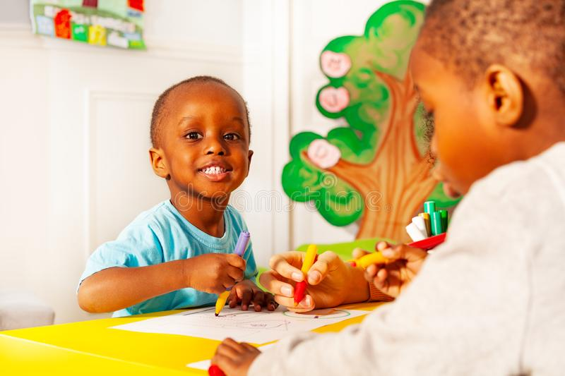 Two little kids draw pictures in nursery school royalty free stock photos
