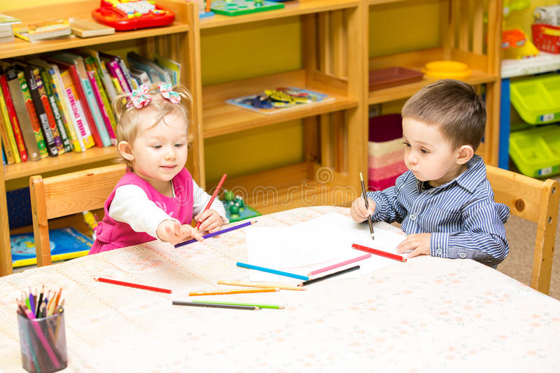 Two little kids drawing with colorful pencils in preschool at the table. royalty free stock photos