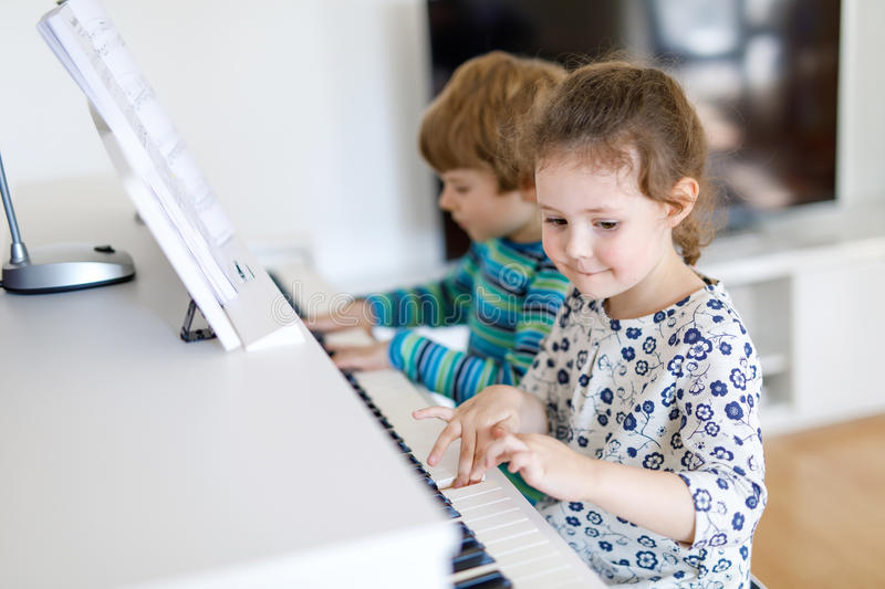 Two little kids girl and boy playing piano in living room or music school stock photos