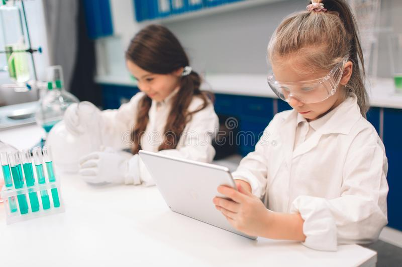 Two little kids in lab coat learning chemistry in school laboratory. Young scientists in protective glasses making royalty free stock image